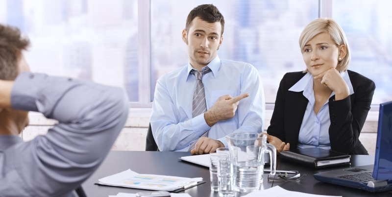 businessman pointing a blaming finger at a female colleague while sitting in a meeting