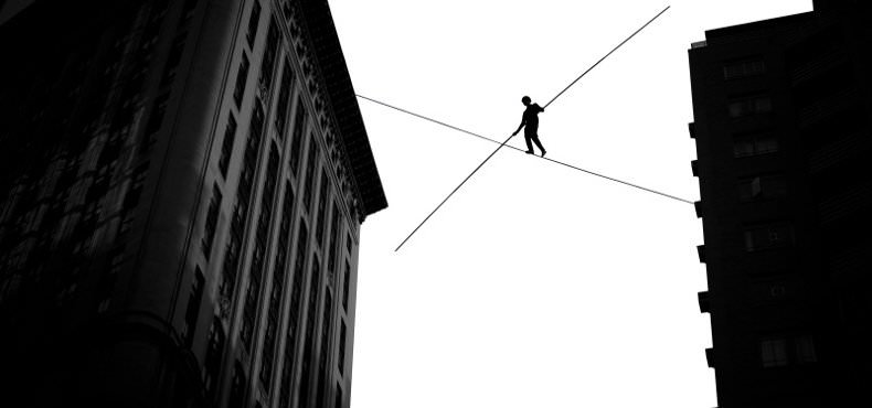 tightrope walker going between city buildings, shows balance between employee autonomy and accountability
