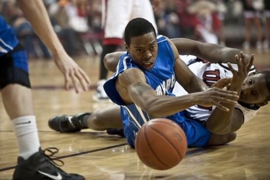 basketball players straining to grab a loose ball