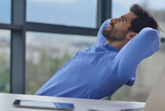 businessman leaning back in his chair with his hands behind his head
