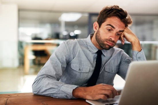 disengaged employee sitting in front of his laptop looking bored