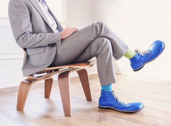 businessman in a suit with clown shoes sitting in a chair - example of promoting the wrong people