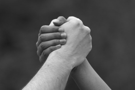 closeup of two people grasping hands to show the power of a positive word