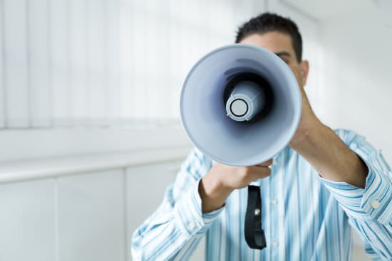 businessman speaking into a megaphone, repeating himself to his employees