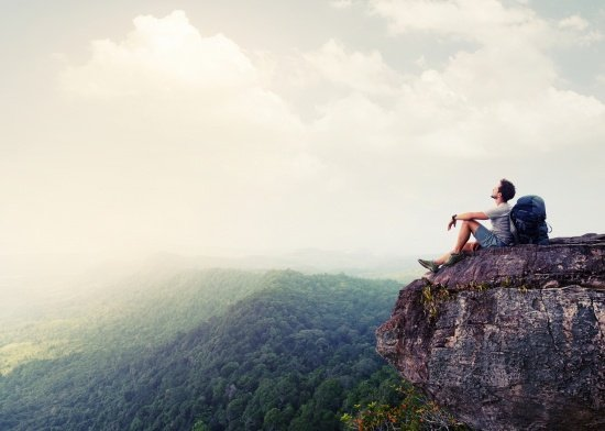 backpacker resting on an outcropping, illustrates the power of delegating